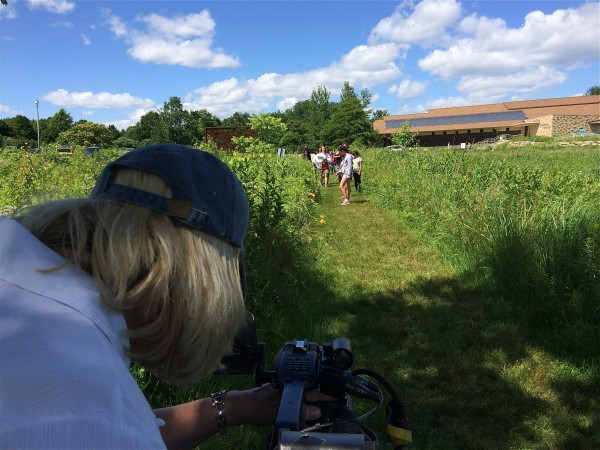 Filming the children as they sweep the prairie to  explore the insect population.